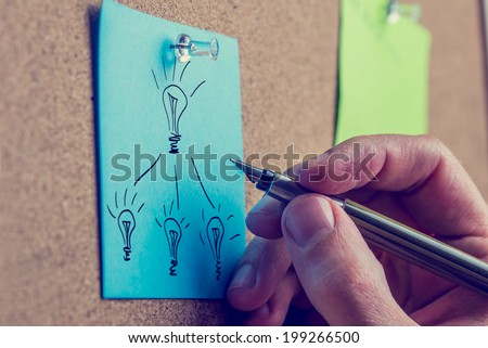 Retro image of the hand of a man working on a business plan writing on a blue sheet of paper on a notice board drawing a flow chart with light bulbs representing bright ideas. - stock photo