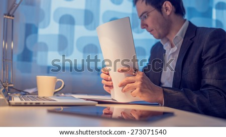 Retro Image of Thoughtful Young  Businessman Filling Documents at his Desk with Laptop and a Cup for Coffee. Captured Inside the Office, Focus to the Documents. - stock photo