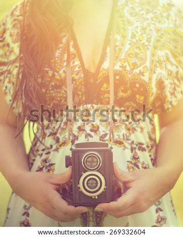 Retro image of woman hands holding vintage camera outdoors - stock photo