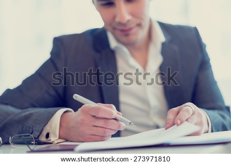 Retro image of young confident lawyer or businessman about to sign a contract or agreement. - stock photo