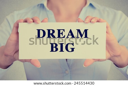 Retro instagram style image businesswoman hands holding white card with dream big phrase text sign isolated on grey wall office background. - stock photo