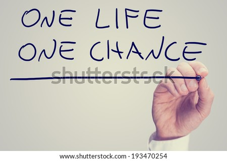 Retro instagram style image of a male hand writing phrase One life one chance on virtual screen.