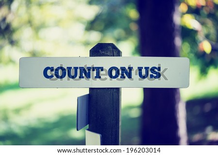 Retro instagram style image of a reassuring message Count on us written on wooden signpost in wooodland. - stock photo