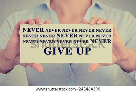 Retro Instagram vintage style image of businesswoman hands holding white card with never give up sign message isolated on grey wall office background. - stock photo