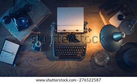 Retro journalist's desk 1950s style with vintage typewriter, phone and lamp at night time, top view