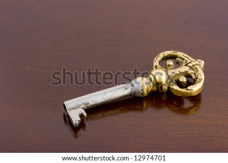 Retro key on wooden table, abstract background - stock photo