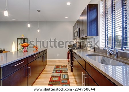 Retro kitchen with modern twist along with hardwood floor, and glossy counters. - stock photo