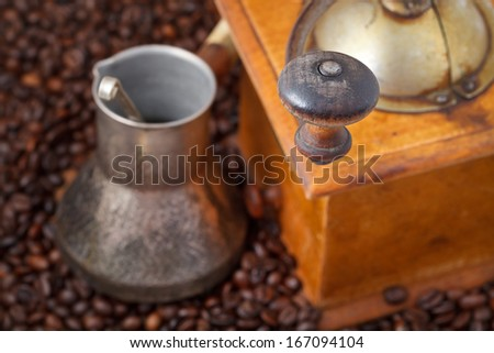retro manual coffee mill and copper pot on many roasted coffee beans