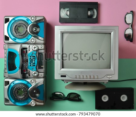 Retro media and entertainment technology from the 80s. Cassette tape recorder, tv, video cassette, 3d glasses on a pink blue pastel background. Memphis style. Flat lay. Top view.