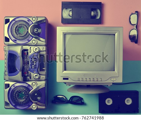 Retro media technologies. Entertainment 80s. Black white lamp TV, tape recorder, video cassette, 3d glasses on a  pastel background. Top view. Flat lay.