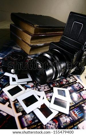 Retro Medium Format Film Camera and Paraphernalia. A photo of a retro medium format film camera with contact sheets, slide films, light meter and books. - stock photo