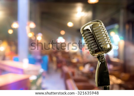Retro microphone against blur colorful light restaurant background - stock photo