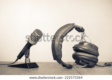 Retro microphone and headphones on table. Vintage old style sepia photography - stock photo