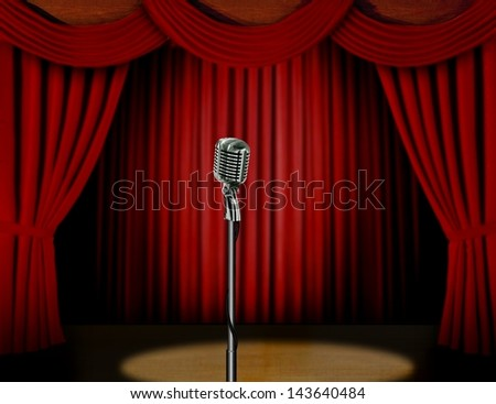 Retro microphone and red curtain on a stage with spotlight - stock photo