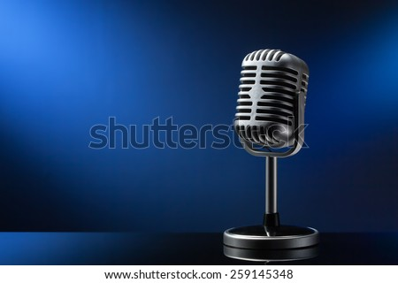 Retro microphone on blue background - stock photo