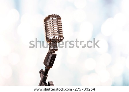 Retro microphone on bright blurred background - stock photo