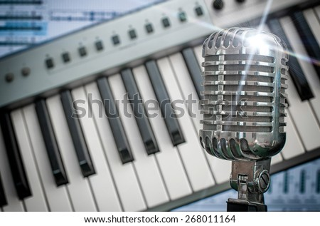 Retro microphone over piano and recording software background. - stock photo