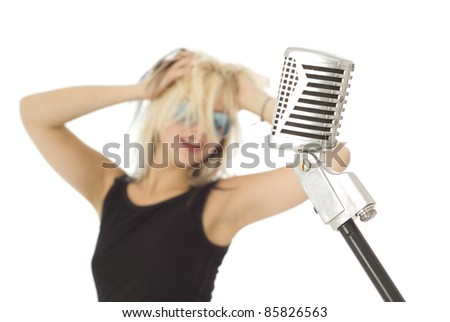 Retro microphone with rocking singer and sunglasses out of focus in background