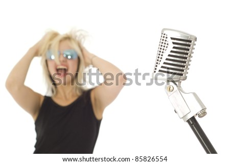 Retro microphone with rocking singer out of focus in background