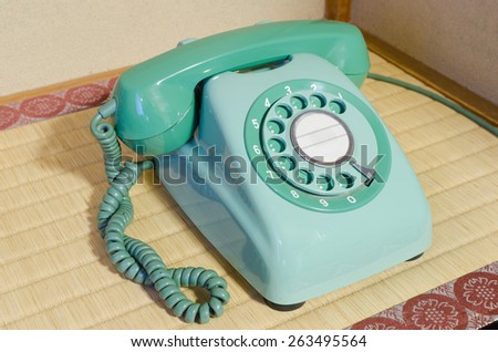 Retro mint green rotary telephone on table.