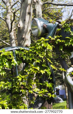 Retro motorcycle exhibition overgrown with ivy. Since the nature of technological change displaces.