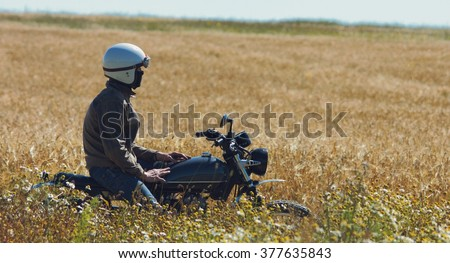 Retro motorcyclist riding in the middle of the field.