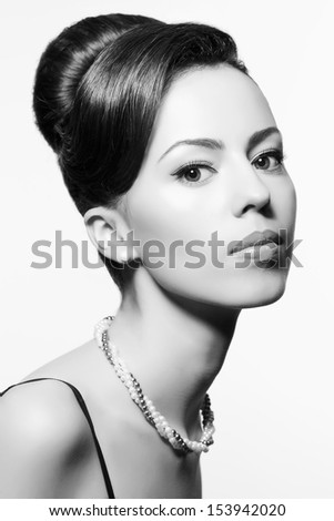 Retro movie star concept. Portrait of beautiful actress in a great black cocktail dress smoking a cigarette with holder. Perfect shiny smile & skin. Vintage (old Hollywood) style. Close up. Copy-space - stock photo