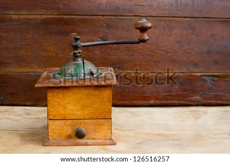 retro old coffee grinder with vintage wooden background