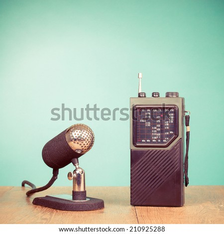 Retro old microphone and portable radio front mint green background - stock photo