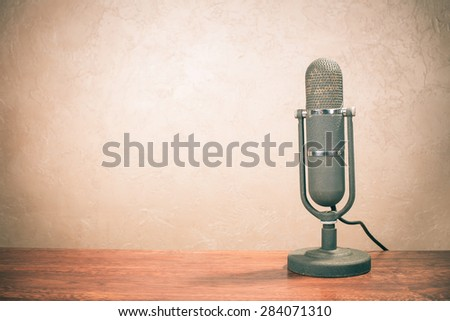 Retro old microphone for broadcasting or recording from 50s on table. Vintage instagram style filtered photo - stock photo