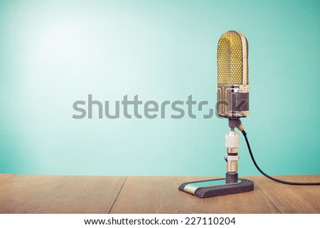 Retro old microphone front mint green background - stock photo