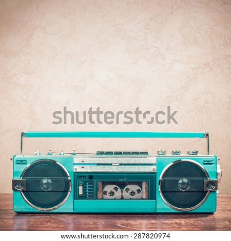 Retro old mint green radio recorder from 80s front grunge background. Vintage style instagram filtered photo