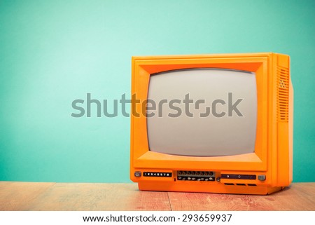 Retro old orange TV receiver front turquoise wall background