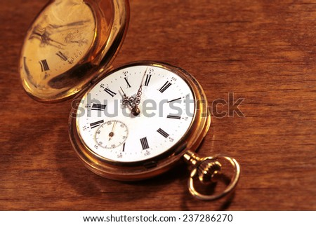 Retro old pocket watch on a wooden background