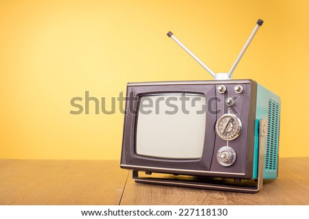 Retro old portable television from 80s front gradient yellow background - stock photo