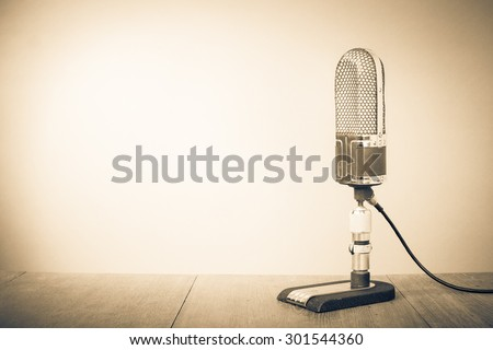 Retro old recording studio microphone from 50s on table. Vintage style sepia photo - stock photo