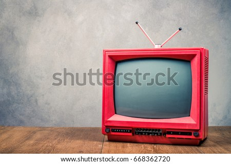 Retro old  red TV receiver on table front textured concrete wall background. Broadcasting concept. Vintage style filtered photo