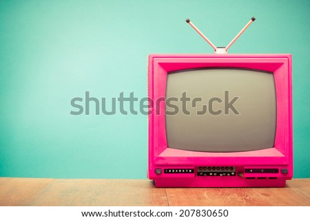 Retro old television from 80s front mint green wall background - stock photo
