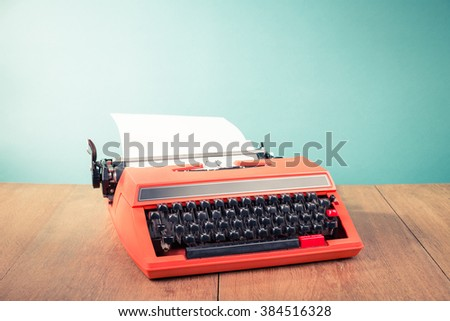 Retro old typewriter with paper on wooden table front mint green background. Vintage style filtered photo - stock photo