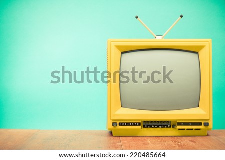 Retro old yellow TV front turquoise wall background - stock photo