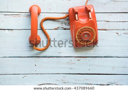 Retro orange-red telephone on the old wooden table with copy space for text or your subject in the past. - stock photo