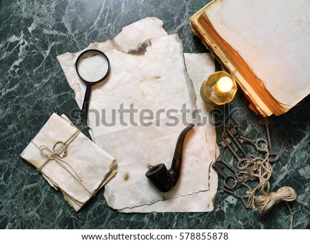 retro papers and book on detective work table with tools background
