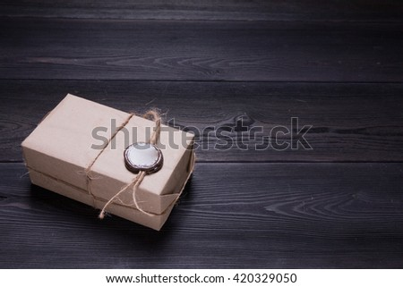 retro parcel with wax seal on thread on black wooden background