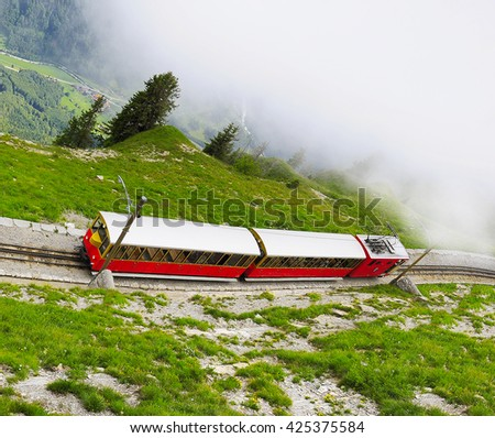 Retro passenger train moves from Schynige Platte to Interlaken at foggy day time. Switzerland. - stock photo