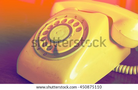 Retro pastel telephone on wooden table with color filters - stock photo