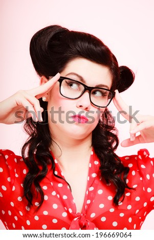 Retro. Pensive stylish woman student or teacher in eyeglasses on pink. Thoughtful girl in pinup style. Education. - stock photo