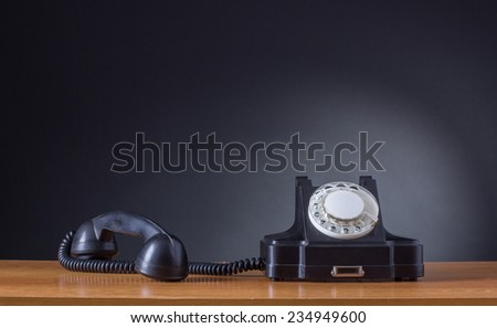 Retro phone in standby mode. Black retro phone on a dark background. - stock photo