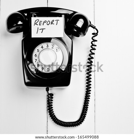 Retro phone with report it message - stock photo