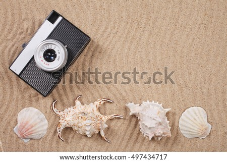 Retro photo camera with shells on the sand