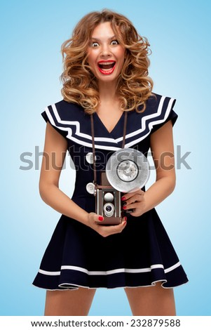 Retro photo of a fashionable pin-up sailor girl with an old vintage photo camera with bulb flash winking to the camera on blue background. - stock photo
